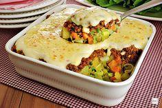 Na foto, a receita de carne moída gratinada com legumes aparece em uma travessa de vidro quadrada. Uma colher retira parte da receita e revela as camadas de requeijão cremoso, carne e legumes.
