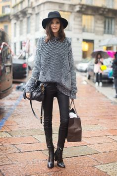 Black and white sweater, black pants, boots and hat.
