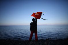 Carl Court / Getty. caption: A woman waves a life jacket to direct a migrant boat ashore as it makes the crossing from Turkey to the Greek island of Lesbos, on November 12, 2015, in Sikaminias, Greece. Rafts and boats continue to make the journey from Turkey to Lesbos each day as thousands flee conflict in Iraq, Syria, Afghanistan, and other countries. Over 500,000 migrants have entered Europe so far this year and approximately four-fifths of those have paid to be smuggled by sea to Greece…