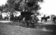 The Soviet KV-2, possibly the largest operational tank in the world in 1941, stranded by the road and overtaken by horse-drawn units of the German army