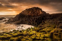 The Giants Causeway is a region located at the tip of Northern Ireland . The strong glow of the evening sunset is reflecting of the volcanic rocks.