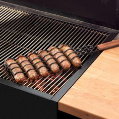 Grilling for a crowd? The BBQ Sausage Basket is your answer for getting the job done. The non-stick coated basket with adjustable height holds six sausages or hot dogs firmly in place. One flip turns them all! Place sausages in basket, latch top and place on the grill. Rosewood handle stays cool longer and keeps hands away from the heat of the grill. $12.95