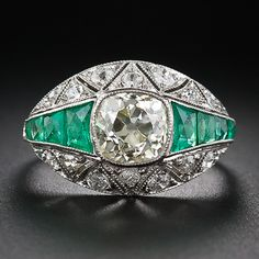 A light yellow European cut diamond weighing 1.90 carats is the center of attraction in this distinctive Art Deco diamond engagement ring embellished with bright green emeralds and small diamonds. This substantial and opulent diamond ring has a gently rolling dome shape setting which closely hugs the finger. A timeless head turner, circa 1920s - 30s.