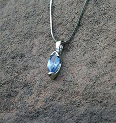 Light aquamarine colored gemstone pendant in silver setting on a silver chain necklace