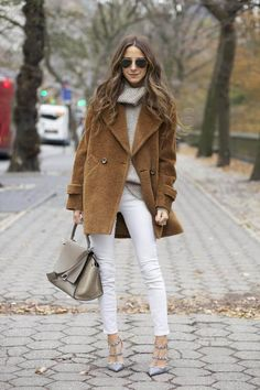 Woman wearing white jeans, a gray turtleneck, and a brown coat