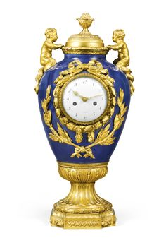 AN EMPIRE ORMOLU-MOUNTED PARIS PORCELAIN MANTEL CLOCK, FRENCH, CIRCA 1800 4½-inch enamel dial inscribed A Paris, bell striking movement with star-cut outside count wheel and later Brocot suspension, mounted within a restored dark blue porcelain urn with lid and finial surmount above metamorphic putti and laurel mounts, the base with concave corners