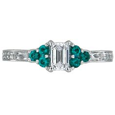 Hand-Engraved Emerald Trio    Clusters of emeralds sit on either side of a beautiful emerald cut diamond and hand engraved vines adorn the band on three sides.    Prices starting at CAD 3,075