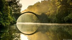 The bridge that was built in 1860 at the Rhododendron Park Kromlau, Gablenz, Germany. Amazing optical illusion!