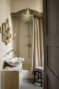 Gorgeous wall color, looks lime washed. Sink is marble shell shape, spout comes out of wall and has 2 faucets, base is concrete and painted in same texture as wall. Shower has beautiful carved wood piece at top. Shower curtain same color as wall. Small crystal candle chandelier, floor is concrete?, painted grey. Love aged mirror and sconces.