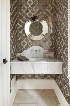 Clad in dark taupe geometric wallpaper, this contemporary powder room boasts a floating marble washstand fit when an oval sink and a polished nickel faucet mounted to a curved marble backsplash fixed beneath a round mirror tiled mirror lit by a brass chain glass light pendants.