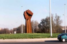 Foto van beeld van grote rode vuist op rotonde.