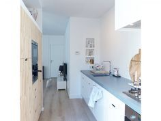 Witte keuken zonder achterwand. Simpel: 3 lagen betonverf voor garagevloeren. Eerst een paar dagen laten uitharden.