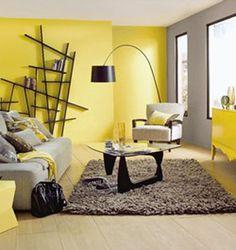 Une belle luminosité dans ce salon autour du jaune et du gris. Sur le mur qui entoure les fenêtres un gris perle illuminé par le buffet bas d'un jaune vif finition laque