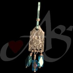 """This is made with copper then hand-stamped and hand cut. On top of being stamped for texture, the word """"JOY"""" is stamped into the center of the zipper pull. Hanging from the bottom of the zipper pull, on copper wire, are three turquoise-colored tube aurora borealis Swarovski crystals."""