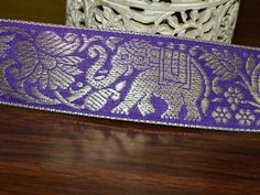 Beautiful Purple Color Jacquard ribbon border trim with Elephant Pattern. Trim is decorated with silver color metallic thread embroidery.   This stunning lace can be used for designing stylish...