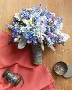 A delicate bouquet of delphinium, grape hyacinth, white ginger, and dusty miller.
