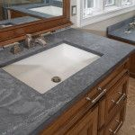 The double vanity in this traditional design in Bryn Mawr, PA features Kohler Kathryn undermount sinks, brushed nickel Delta lavatory faucets, and honed Pietra Di Cardosa limestone countertops.