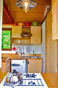 Open kitchen plan with bathroom behind kitchen.  Keeps the whole space from kitchen to living room more open and not chopped up.  From the Tall Mans Tiny House
