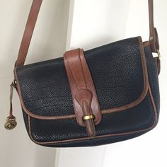 Classic Dooney & Bourke vintage cross body bag Classic & coveted black & brown leather 70s Dooney cross body bag w/solid brass hard wear. Perfect for festivals! See pix for worn leather on bag piping, has inner zipped pocket and card slots. Something has spilt in outer back pocket of purse so it's a little sticky but totally usable, as spil is dark it is not showing up on pix but it has not effected outer bag leather as pix show. Not a glossy new item but is perfect if you seek the worn in…