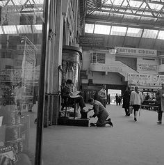 Looking past a shop window on the concourse at Waterloo Station towards a shoeshine man cleaning the shoes of a seated City gent who is reading his newspaper Local History, British History, Old Pictures, Old Photos, Waterloo Station, East End London, Shops, Seen, Greater London