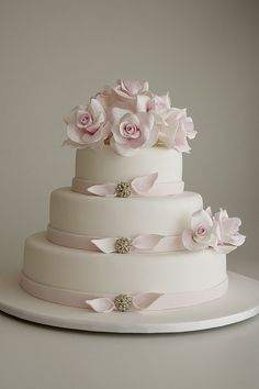 Wedding cake with pink sugar roses and bows with jewelry accents