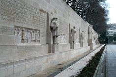 """The Reformation Wall in Geneva, (1909-1917). 15' statues of:  1. Guillaume Farel - 1st to preach the Reformation in Geneva  2. John Calvin - leader of Reformation movement & spiritual father of Geneva  3. Theodore Beza - Calvin's successor  4. John Knox - Friend of Calvin & founder of Presbyterianism in Scotland.  Behind the statues runs the motto: Post Tenebras Lux (""""After Darkness, Light"""").  Includes Roger Williams & the pilgrim fathers, Martin Luther, & Ulrich Zwingli."""
