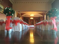 The Grand Ballroom, Haigh Hall dressed in red and white.  White chair covers with red sash.  The bay trees are dressed in red and white roses with a matching red bow.  www.am-flowers.co.uk