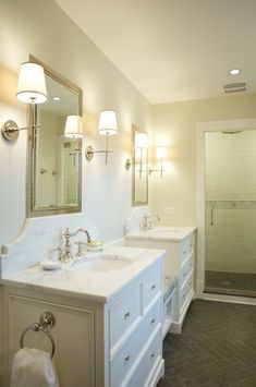 source: Scott Lyon & Company Stunning ensuite with Visual Comfort Lightings 'Bryant Sconces' and Polished Nickel Framed Medicine Cabinets from Restoration Hardware. Pair of white bathroom vanities with built-in bench seating area. Gray herringbone slate tile floor