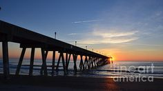 "This beautiful scene of the ""1st Sunrise Of 2015'' was photographed by Bob Sample of PKS Images at Mercers Pier on Wrightsville Beach NC as the sun was making it's first appearance of the new year. With the wispy clouds and the reflection of the sun cascading across the waves to shore, it was a very peaceful and calming way to usher in the new year. This photograph was captured using a 16 x 9 ratio and is an excellent panoramic offering"