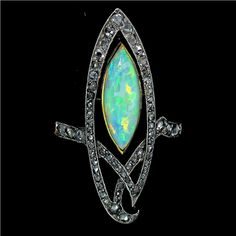 1900s Art Nouveau chevron style ring features a marquise opal surrounded by rose cut diamonds and set in platinum and 18 karat yellow gold | JV