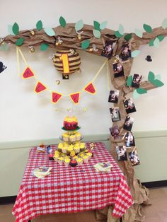 Tree with Bee hive and his monthly photos going up the trunk for his 1 year birthday pooh themed party! The cake was a smash cake on top that looked like honey pot and cupcakes for bottom two rows!