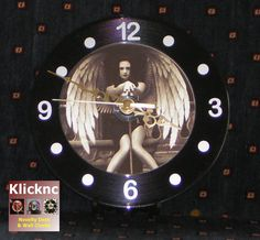 https://www.etsy.com/uk/listing/509730662/dark-angel-18cm-desk-or-wall-clock  A lovely sepia design featuring a beautiful winged dark angel holding the Sword of the Damned. Printed on a CD and attached to an up-cycled 18cm 45rpm vinyl record, it features a quarter-hour clock dial in silver and an aluminium ornate Serpantine-stlye handset in gold  Designed for shelf or wall hanging, the clock comes with a built-in hook and a recycled plastic stand enabling it to be placed on any flat surface…