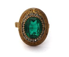 Art Deco Emerald Glass Ring  A lovely 1920's to 1930's era ring with a big, glittering, faceted emerald green glass oval stone flanked by small glass rhinestones. This lovely ring is made of brass and has an etched floral motif on the face, with cool stair-stepped shoulders.  It's a super wearable size 8, and most likely Czech in origin, though unmarked.   www.revivalcultvintage.com