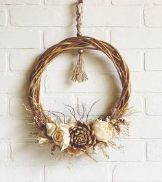 round seashell floral wreath in the softer shades of summer gold...cream...grey a round straw wreath lightly painted in gold with some of the natural straw color still showing through lightly washed in grey beautiful natural dried florals and leaves in soft shades of cream, sage, soft brown and