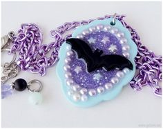 A sweet Pastel Goth inspired creation, featuring a pastel aqua blue resin pendant, filled with iridescent purple glitter, adorned with pearl decorations,