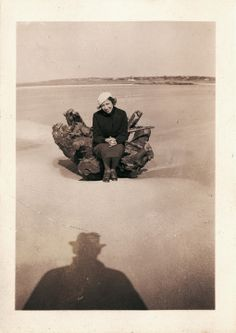 Vintage Snapshot Photo | Collection of Guy Saunders. Woman sitting on driftwood stump, ominous shadow of man wearing hat.