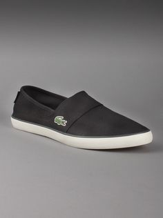 Lacoste® Mens Marice Canvas Sneakers in Black.  Enjoy the casual comfort of these Lacoste canvas sneakers any day of the week. Mens black slip on shoes have canvas uppers, a textile lining and that signature crocodile logo on the side of each shoes. A great laid-back look with jeans or shorts.