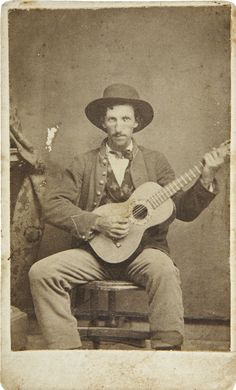 Union Civil War Infantry Enlisted Man Sitting with Guitar. He is wearing infantry jacket over unusual flowered vest with large brim slouch hat.