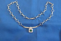 18ct white gold emerald and diamond pendant on had made chain with diamond set bar.