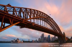 Sydney Harbour Bridge at Sunset, Sydney, New South Wales (NSW), Australia. The Sydney Harbour Bridge (Sydney's greatest tourism icon) - on a par with San Francisco's Golden Gate Bridge, New York's Statue of Liberty, London's Tower Bridge and the Eiffel Tower in Paris - took eight years to build and opened in March 1932. It also sometimes known as the 'coat hanger' or simply called 'The Bridge' by Sydneysiders. It has become an Australian icon. Not only is it a symbol of the incredible…