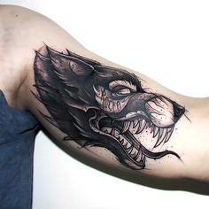 A great wolf head tattoo idea made in sketch style and placed on the man's bicep. Style: Sketch. Color: Gray. Tags: Best
