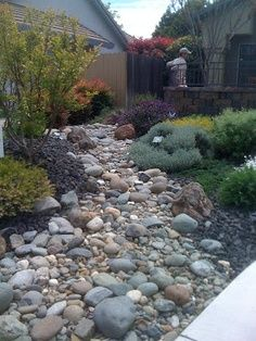 dry creek bed for drainage - off the side of the porch in between the garden and the yard