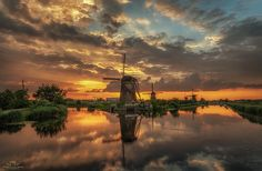 """Reflections of Kinderdijk II - A beautiful golden hour at Kinderdijk standing on the main bridge. Classic but always a wonderful happening if the weather conditions are in your favor.  Best viewed on black (click image or press """"M"""")  Facebook : https://www.facebook.com/hermanvdberge.photography Instagram : https://www.instagram.com/herman_van_den_berge/"""