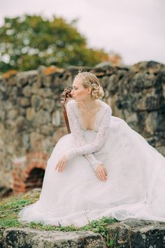 Styled Bridal Shoot in Finland.    Photography: Petra Veikkola Photography Bridal gown: Pukuni Bridal Adornments: AINO Styling & Consept: AINO / Satu & Pukuni / Saara Make-up: Mona's Daily Style Hair: Hanna Julku Model: Mirka Könnö Rings: AITO Kultasepänverstas Flowers: Kukka Fiori Location: Bishop's Castle at Kuusisto , Finland  Lace back wedding dress, long lace sleeves, bridal gown, long tulle train, veil.
