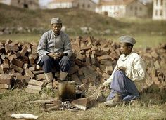 Two French soldiers from Africa heat up a meal on an outdoor fireplace made from brick on the Western Front in 1917. Colour photo (Autochrome Lumière) by Fernand Cuville.