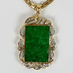 Stamped 18K yellow gold jade and diamond pendant which is bezel set with curved jadeite plaque.