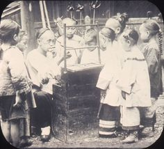 """File:The """"candy man"""" blowing animals out of colored molasses surrounded by children, Changde, Hunan, China, ca.1900-1919 (IMP-YDS-RG008-358-0008-0061).jpg"""