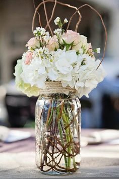 I love this center piece so much and its really simple. Its just twigs, flowers of your choice, twine, and a mason jar