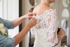 Lace wedding dress being done up during the bridal prep at Coworth Park - top tips to get the best out of your wedding photos on the wedding morning © Fiona Kelly Photography