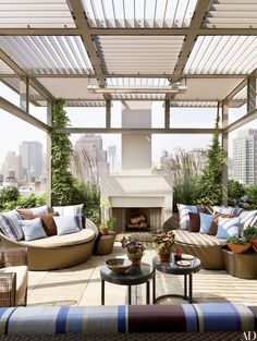 On this Manhattan rooftop terrace, covered by an edgy trellis, a handsome fireplace anchors a sitting area, making it possible to enjoy even the coolest summer nights alfresco. | archdigest.com